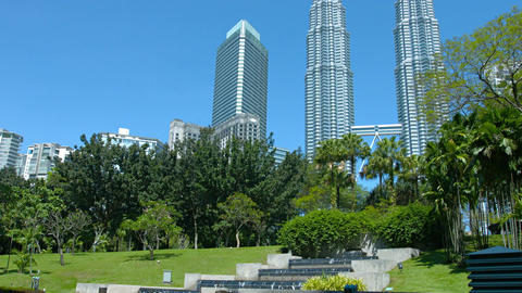 Petronas Twin Towers from KL city park with fountain and green trees 影片素材