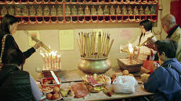 Buddhists lighting joss sticks at an altar inside Man Mo Temple. FullHD video Footage