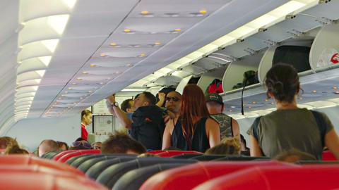 Airline passengers stowing luggage in overhead compartments Footage