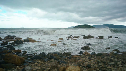 Waves Crash over a Rocky Beach on a Cloudy Day. FullHD video Footage