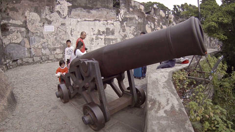 Children playing on enormous. antique cannon atop Fortaleza de Monte in Macau Footage