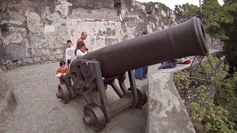 Children playing on enormous. antique cannon atop Fortaleza de Monte in Macau Live Action