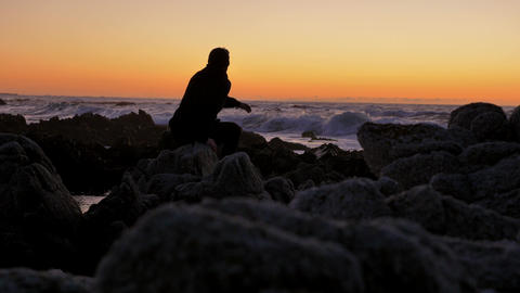Men Relaxing on the rocks watching sunset at pacific coast Live Action