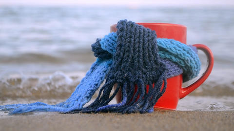 Red mug with coffee tied with blue knitted scarf stands on sandy beach Live Action