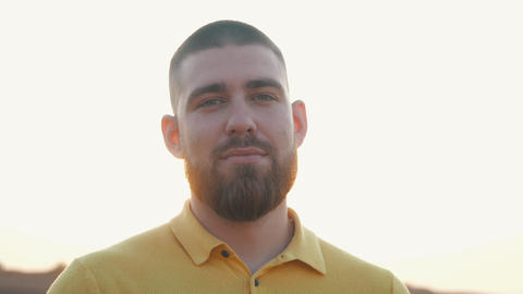 Close-up view of the face of a short-haired bearded man in a yellow polo shirt Live Action