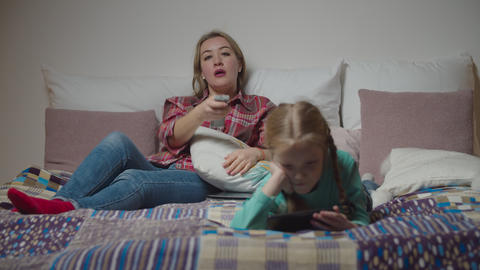 Family with child relaxing on bed in the evening Live Action