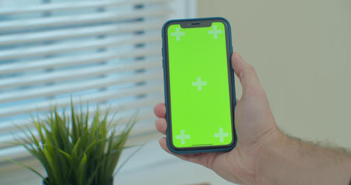 Man using vertical smartphone with green screen. Close-up shot of man's hands Live Action