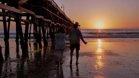 Couple walking away holding hands together at Scenic orange pink Sunset with Live Action