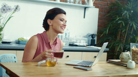 Business woman chatting online on laptop. Girl drinking tea during online call Live Action