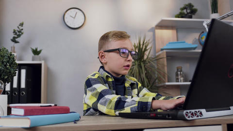 Portrait of attractive teen smart boy in eyeglasses which sitting at his Live Action