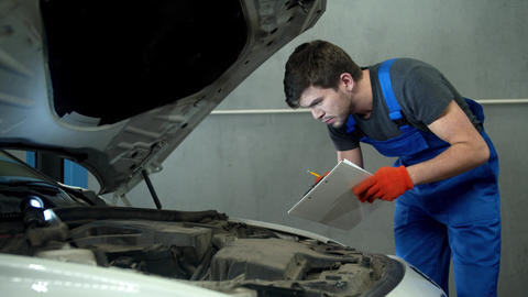 Mechanic examines the motor of car and takes notes Live Action