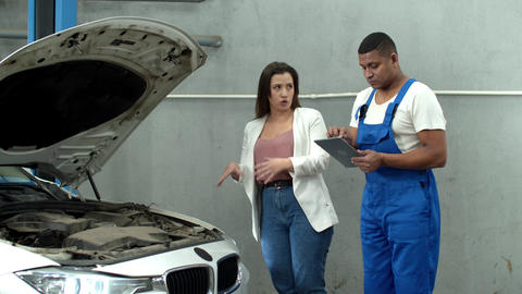 Woman shows the motor of car to mechanic with tablet Live Action