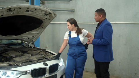 Woman technician shows a car to the owner in auto repair shop Live Action