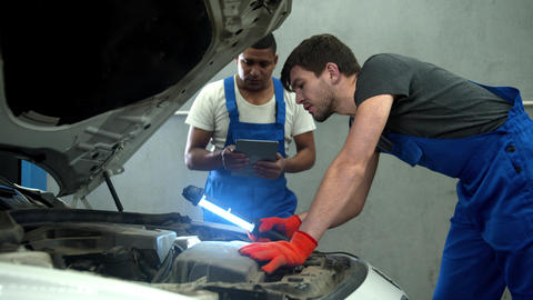 Mechanic with flashlight examines the motor of car and his collegue takes notes Live Action