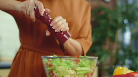 Girl adding spices to vegetable salad. Woman seasoning vegetables in kitchen Live Action