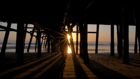 Woman silhouette walking under pier at Scenic orange pink Sunset with epic rays Live Action