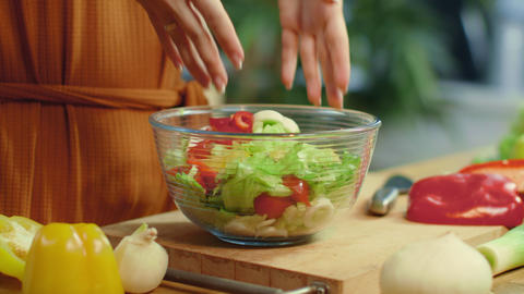 Woman hands mixing vegetables in salad bowl. Girl preparing fresh salad Live Action