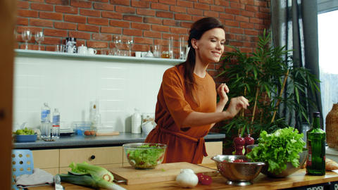 Smiling girl cooking healthy salad at home. Woman tearing lettuce leaves on bowl Live Action