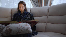 Beautiful teenager girl reads a huge red book while sitting on a sofa in a Live Action