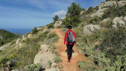 Woman backpacker hiking within mountain trek on Mallorka islan. Sunny spring day with comfortable Live Action