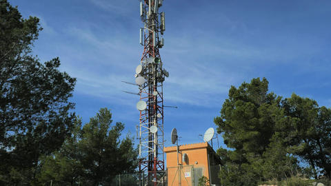Modern tower with huge complex of telecommunication antennas on old bricks house hidden in pine Live Action