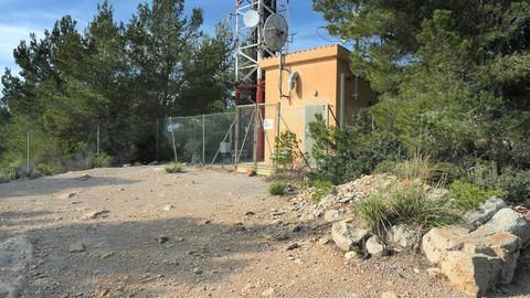 Remote mountain communications center with antennas on steel tower against a deep blue sky Live Action