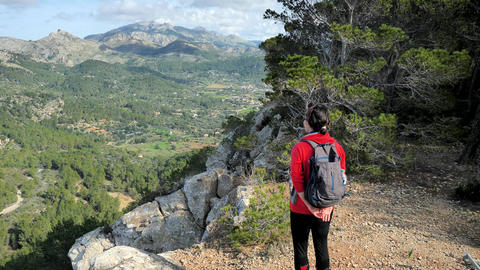 Discovery Travel Destination Concept. Hiker Woman With Backpack on rocky view point in Mallorka Live Action