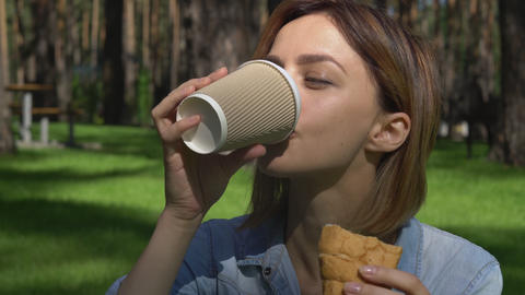 Female eats bakery products at the open air Footage