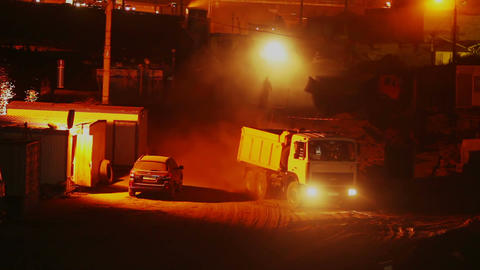Construction site at night, trucks lorries drive in out, yellow Footage