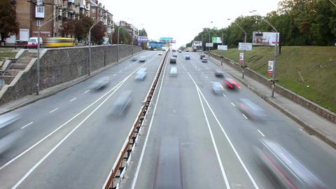Small city street time lapse, cars drive both ways, bridge Footage