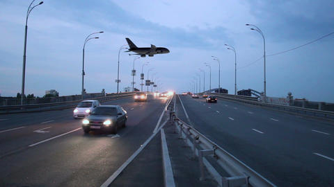 Taking off airplane above highway city road at dusk, lights Footage
