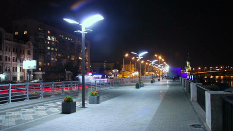 Night city quay, people walking, cars driving, street lights on Footage