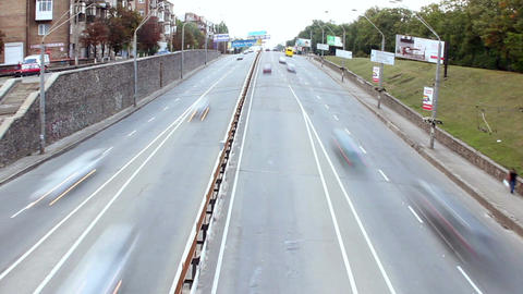 Dolly shot timelapse city traffic, cars drive under bridge, day Footage