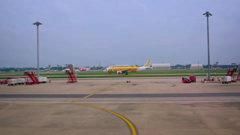 Airliner taxiing past passenger terminal at Don Mueang International Airport Footage