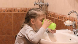 Five-year old girl rinsing mouth after brushing teeth Live Action
