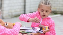 Seven-year girl hard dunks brush in a jar with watercolor paint drawing on the a Footage