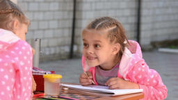 Seven-year girl drawing in an album emotionally speaks with another girl Live Action