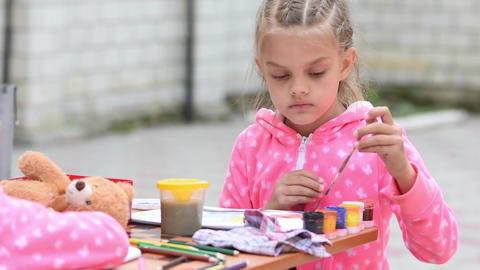 Seven-year girl choose the right color ink drawing in an album, sitting at a tab Live Action