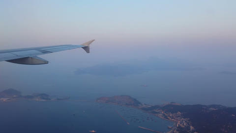 Wing of airplane flying over islands and sea Live Action