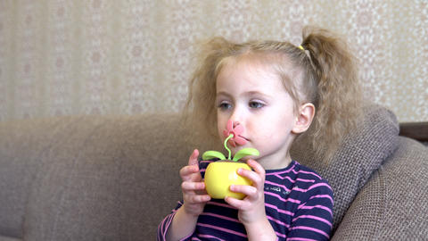 Little girl with a flower toy. Girl sniffs a toy flower. Flower moves from the Live Action