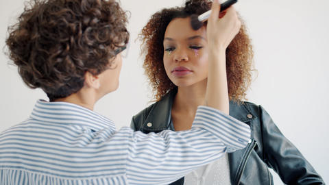 Pretty mixed race model working with make-up artist in studio on white Live Action