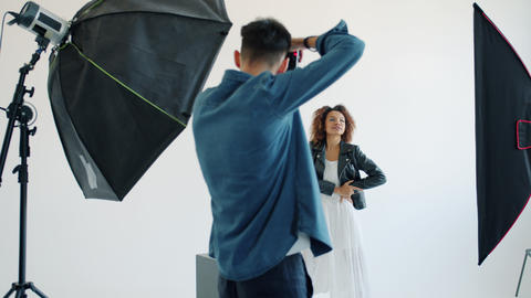 Model mixed race lady and photographer working in studio during photo shoot Live Action