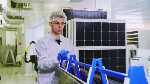 worker in glasses transports solar panels along workshop Live Action