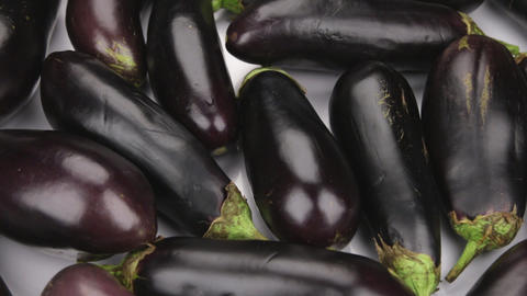 Rotation, a heap of ripe eggplant. Texture of eggplants Live Action