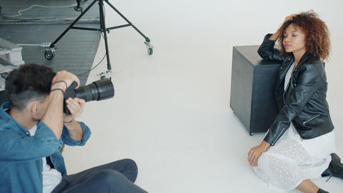Successful photographer taking photo of attractive young lady in modern studio Live Action