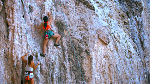 Two female rock climbers slowly climp up the rock with safety belt and ropes Footage