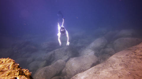Tourist Swims Underwater in the Rocky Shallows with Fish. Video UltraHD Footage