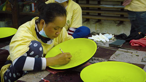 Local woman draws guide lines on a ceramic plate for a painting project Footage