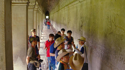 Tour guide explains relief carvings along corridor wall in Angkor Wat Live Action