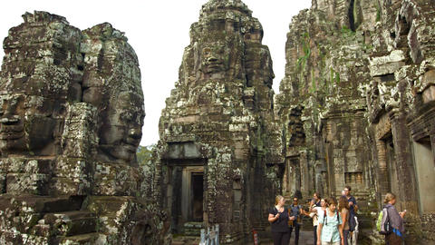 Tourists stroll through ancient courtyard of Bayon Temple in Cambodia Live Action